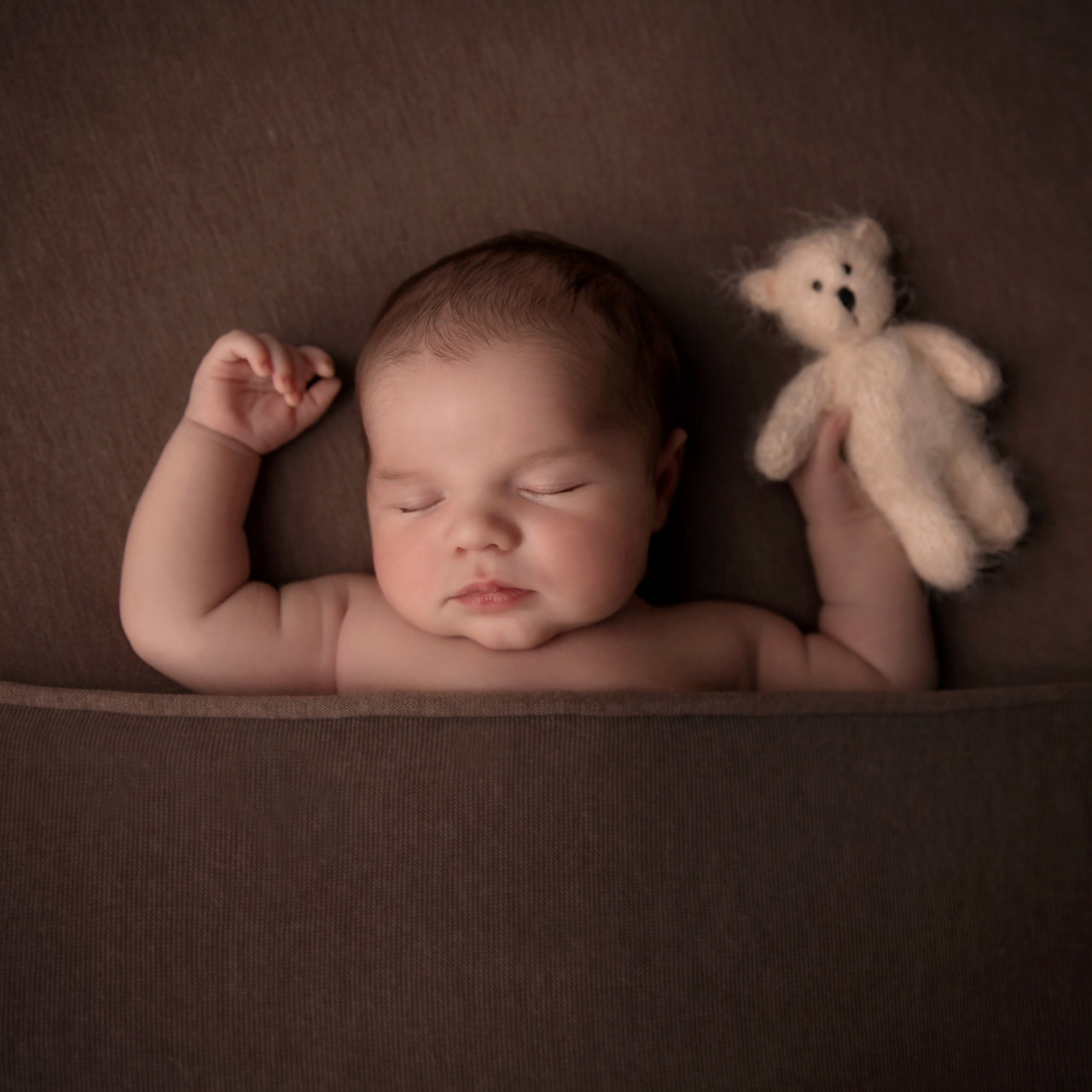 Baby holding bear asleep in tan
