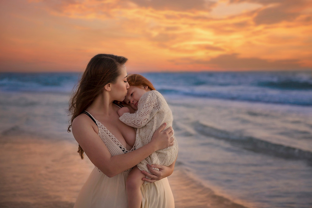Mama kisses daughter at beach during sunset for they lifestyle photo session