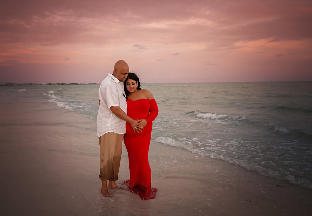Photo of pregnant mother and dad cuddling on the beach in Tampa