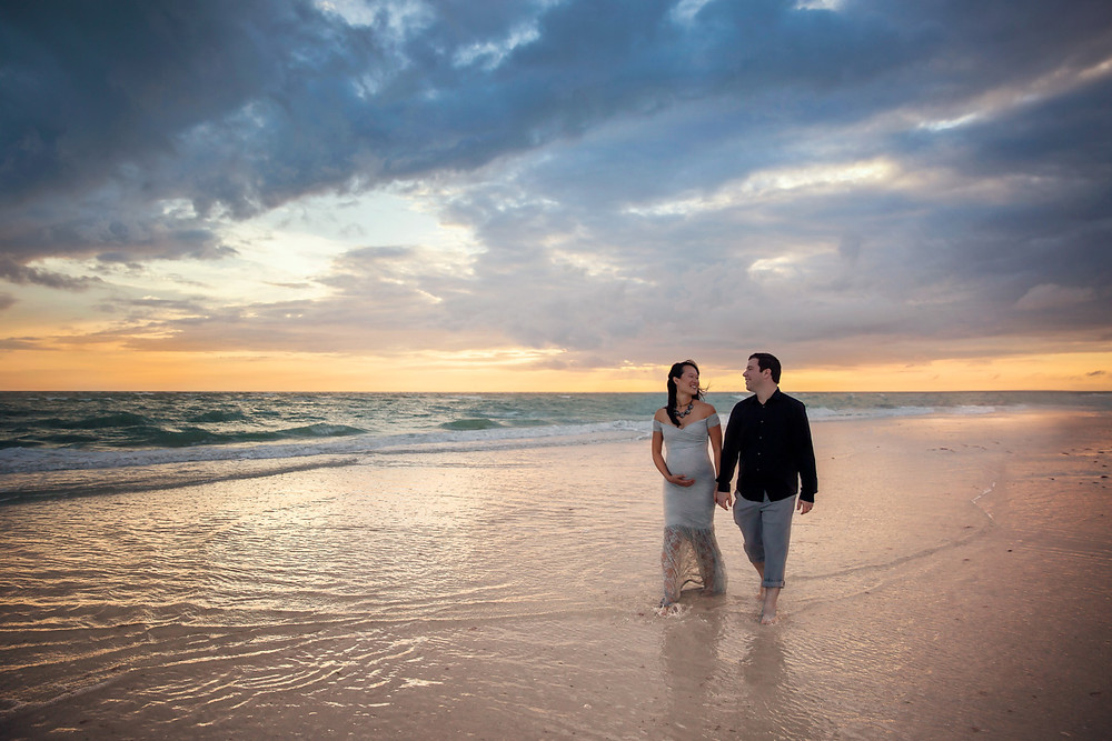 Tampa Maternity photographer photographs expecting Mother and father walking down the beach