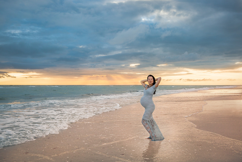 Expecting Mom ont he beach during maternity photos in tampa. She wore a grey dress that matched perfectly with the cloudy sky