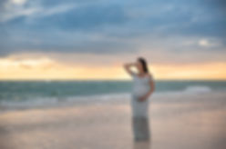 Maternity beach sunset photo of Mom in white gown in Tampa Fl