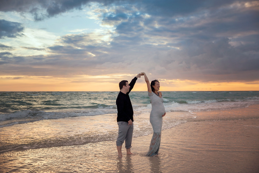Dad twirling Mom during a sunset at the beach for their pregnancy photo ideas