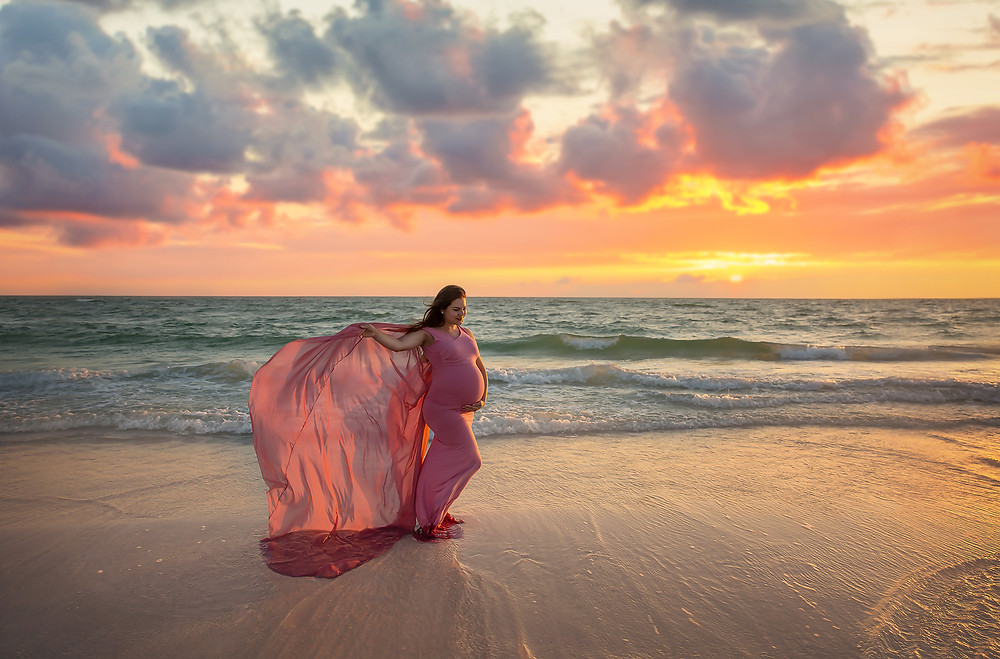 Expecting mother holding flowing gown at sunset on the beach in Tampa wearing a gorgeous pink gown