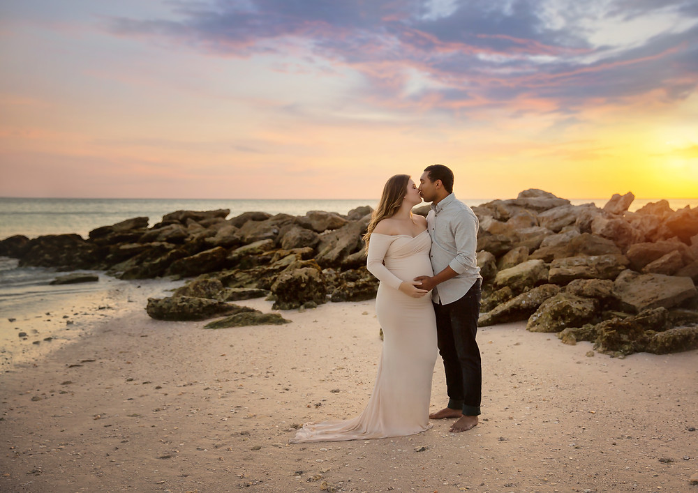 Photo of a couple kissing at the beach during their pregnancy photo shoot!