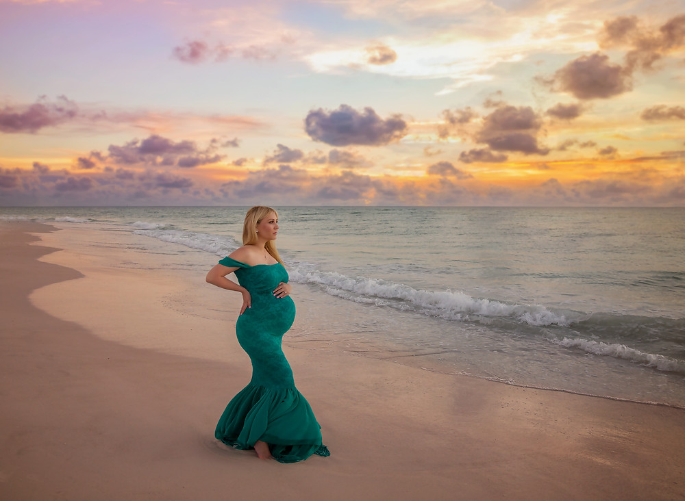 Pregnancy photo taken on the beach in Tampa! This mama is wearing a emerald green maternity gown during sunset!