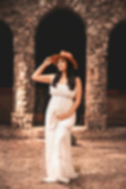 Pregnant mother holding on to hat during pregnancy photo shoot in tampa