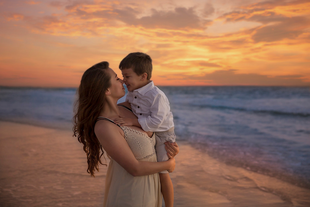 Mother and son giving Eskimo kisses while cuddling during family beach photo shoot