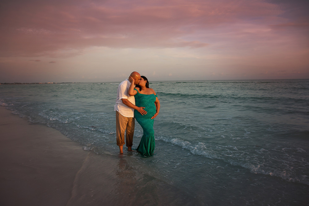 Mother and father kiss each other at Tampa's beautiful beach during sunset
