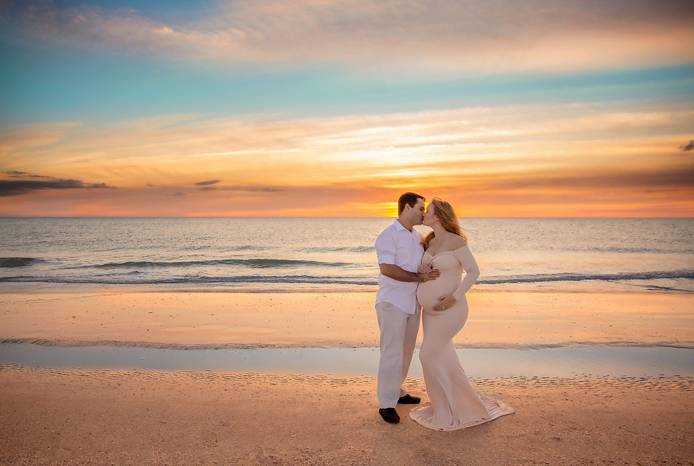 Expecting couple kissing in front of a gorgeous yellow and blue sunset in Tampa Florida