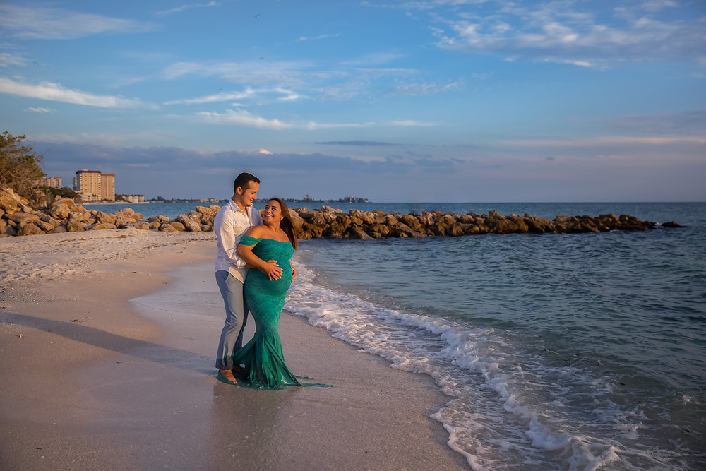 Couple holding each other on the beach. The maternity gown worn is Sew Trendy Accessories- Pregnancy photos on the beach during sunset