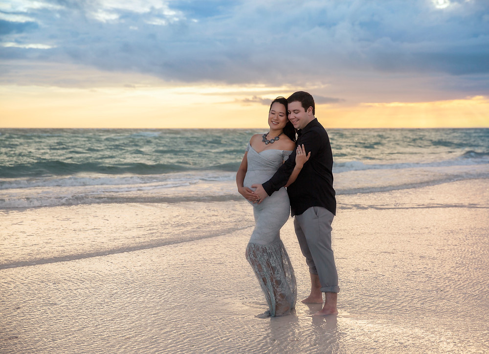 Mom and dad cuddled up during pregnancy photos on the beach in Tampa