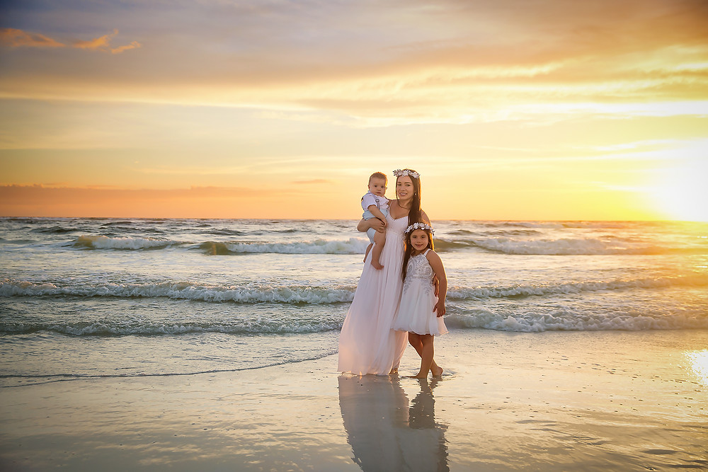 Mother and children at the beach taking sunset photos