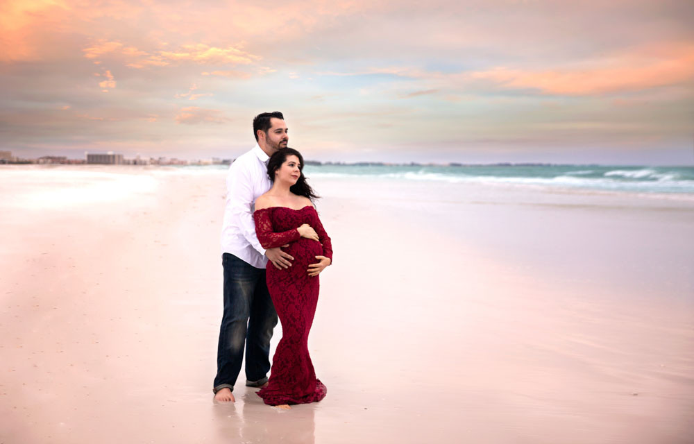 Tampa expecting mother and father cuddled on the beach for maternity photos