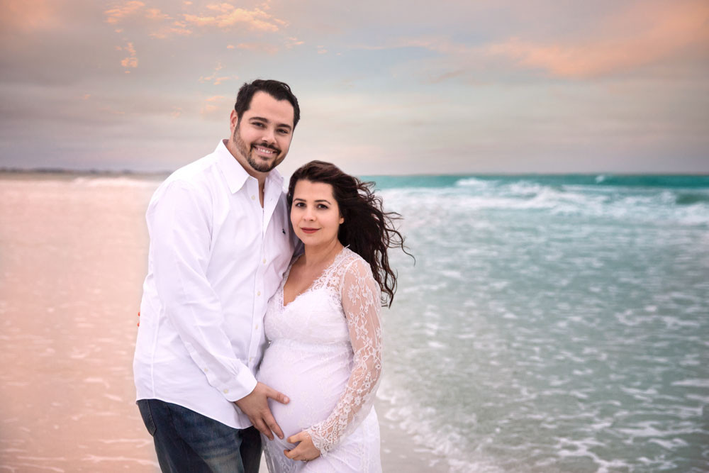 Pregnant mother and Father cuddling on the beach during maternity photos at Siesta Key beach