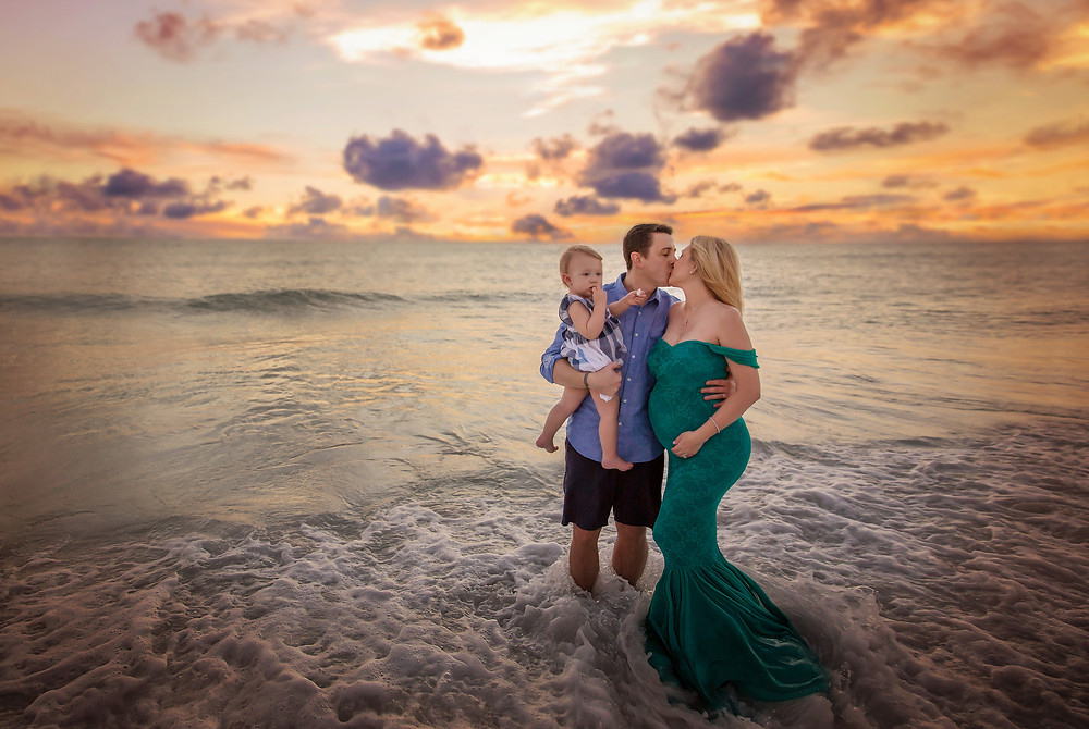 Pregnant mother who is holding her belly and kissing her husband and daughter during their maternity photo session in Tampa