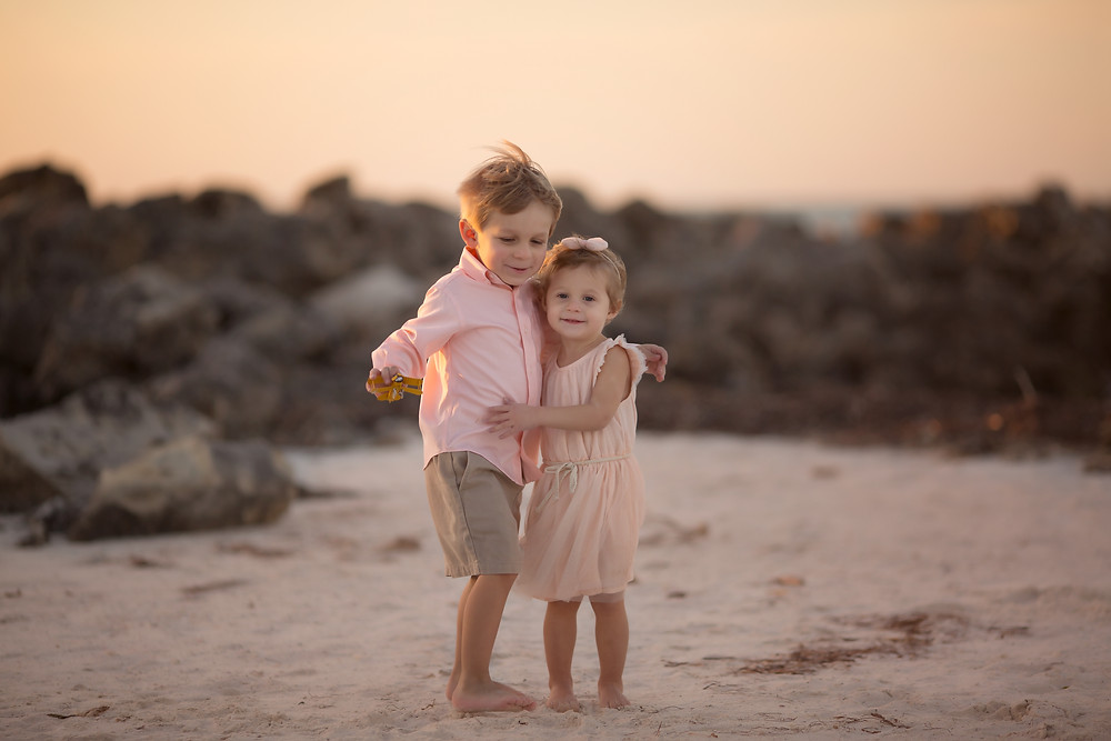 Brother and sister hugging at the beach
