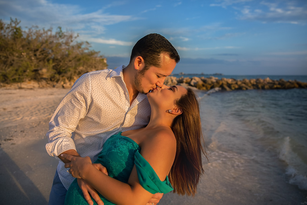 Dad and Mom kissing on the beach for their maternity and pregnancy photos!