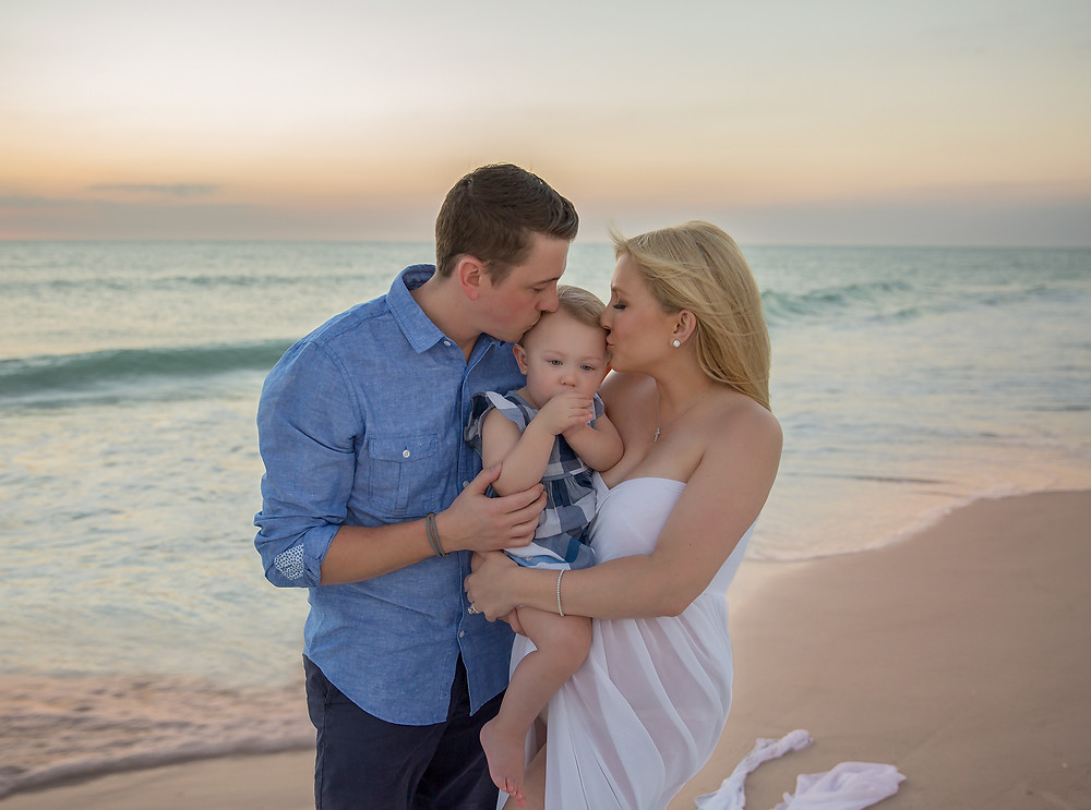 Mom and Dad kissing little girl during pregnancy photos in Tampa