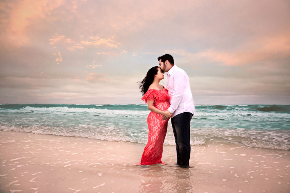 Expecting mother and father cuddled on the beach during maternity photo shoot in tampa