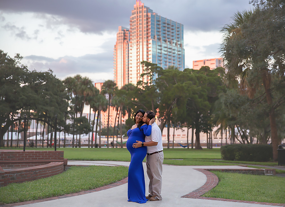 Expecting couple kissing during down town photo session