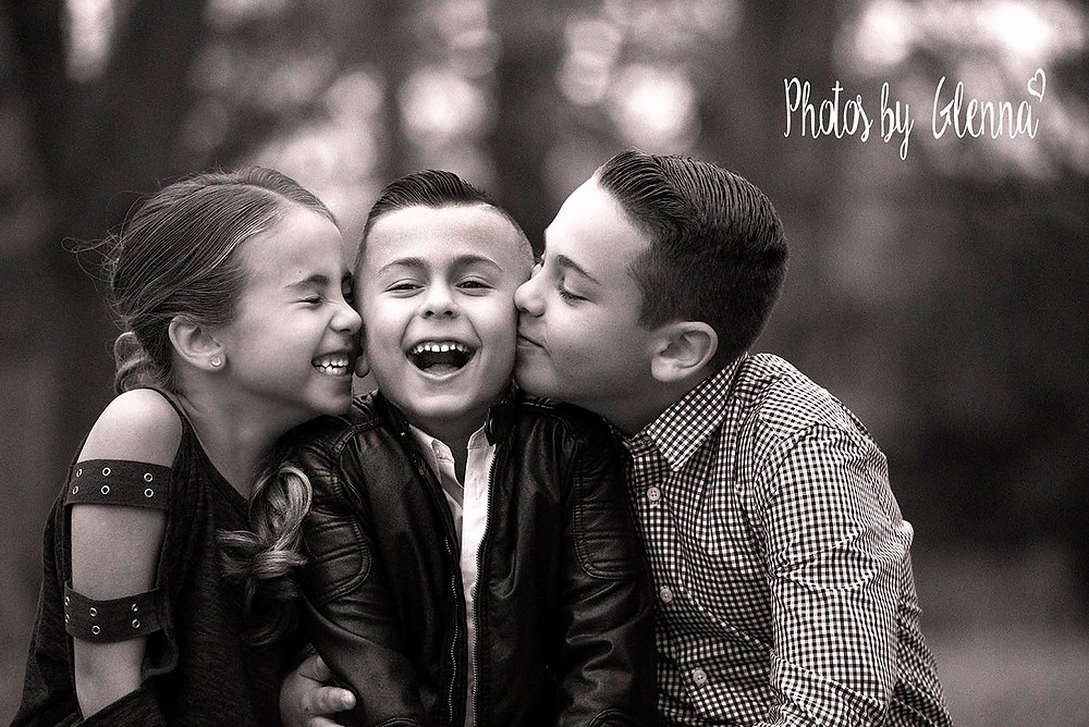 Children kissing each other and giggling in photo taken by Photos by Glenna