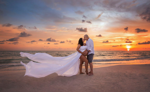 Maternity photo in tampa of mother and father kissing in front of a beautiful orange sky with blue clouds.