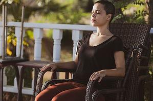 woman-in-black-top-sitting-on-brown-armc