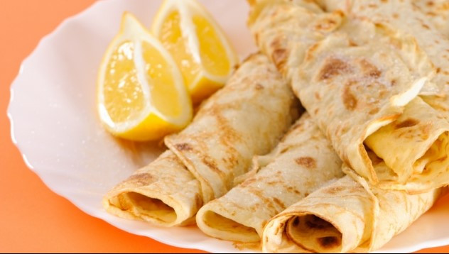 Rolled pancakes on a plate with sliced lemons