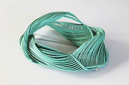 A side view photograph of the mint green Twist Brooch. It is a folded and twisted design in an assymetrical oval shape. The backgrounnd is plain white.