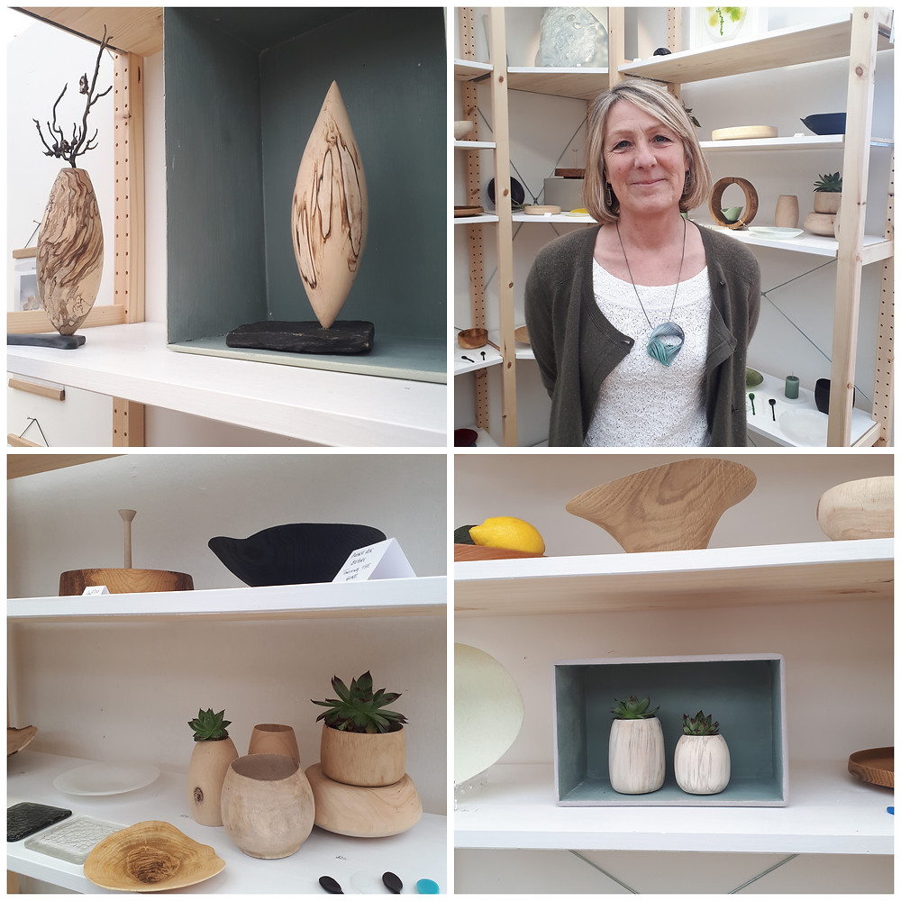 A collection of 4 photos from Jayne Against The Grain display stand at Craft Festival, featuring Jayne's beautiful wooden creations and vessels. The top right hand photo is of Jayne wearing a card pendant made by me. Jayne is a white woman with a short blonde bob, wearing a white crochet top and an olive green cardigan.