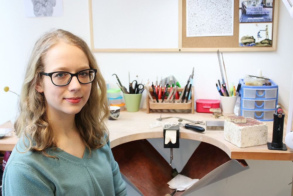 Dominika is a white woman with short blonde wavy hair and thick black glasses. She is wearing a mint green V neck jumper. She is sitting in her studio in front of her jewellery bench. The bench has a plethora of colourful pots and tubs and jewellery tools. There is a white board and drawings on the wall behind her.