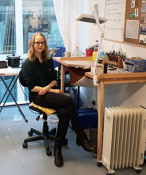 Dominika sitting at her bench in a jewellery studio. She has mid-length blonde hair and thick black glasses, and is wearing a dark green shirt with a small rectangular red pin, pinstripe black trousers and black boots. Her jewellery bench is full of colourful tools and tubs, has a large white lamp clamped to it, and a corkboard and white board is hanging just above it. There is a small white radiator at the front of the shot next to the bench, and a small white table with a black pot behind Dominika. The background has windows that peak into other artist studios.
