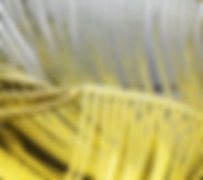 Close up of a linear sculptural brooch in a yellow and grey gradient
