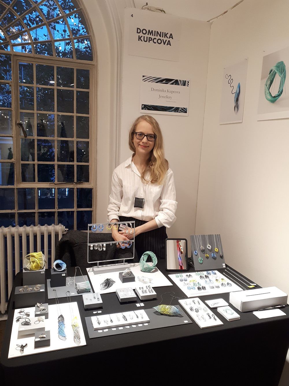 Dominika at her stand at Made London. Dominika is a white woman with mid-length blonde wavy hair and thick black glasses. She is wearing a white shirt, a black cylinder Optical Illusion Pendant, and black pinstripe trousers. She is standing behind a table full of her colourful jewellery, with a black tablecloth and grey wooden blocks. The wall behind her has a sign that says DOMINIKA KUPCOVA, and another one with Dominika Kupcova Jewellery. There are 2 photos on the wall of Dominika's jewellery, the Blue Twist Pendant and the mint green Twist Brooch. The window on the left shows it is evening.