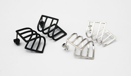 A photo of two pairs of Curve Earrings, matte black oxidised silver pair on the left and polished silver on the right. They are curved linear forms with gaps. The background is plain white.