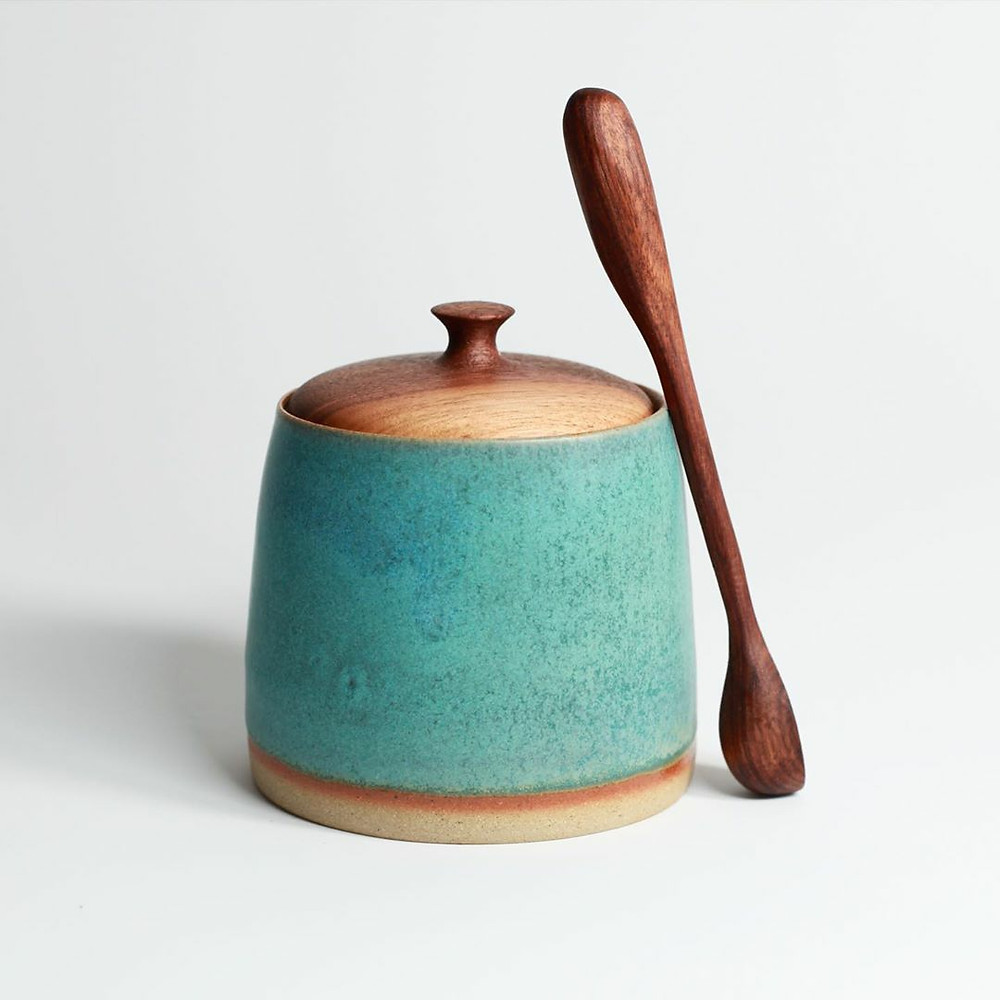 A turquoise jar with a brown line on the bottom, with a hand carved wooden lid. A handmade wooden spoon is resting against the jar. The background is plain white.