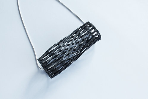 contemporary handmade unique cylinder pendant in a black speckled finish, hanging on a blackened silver chain