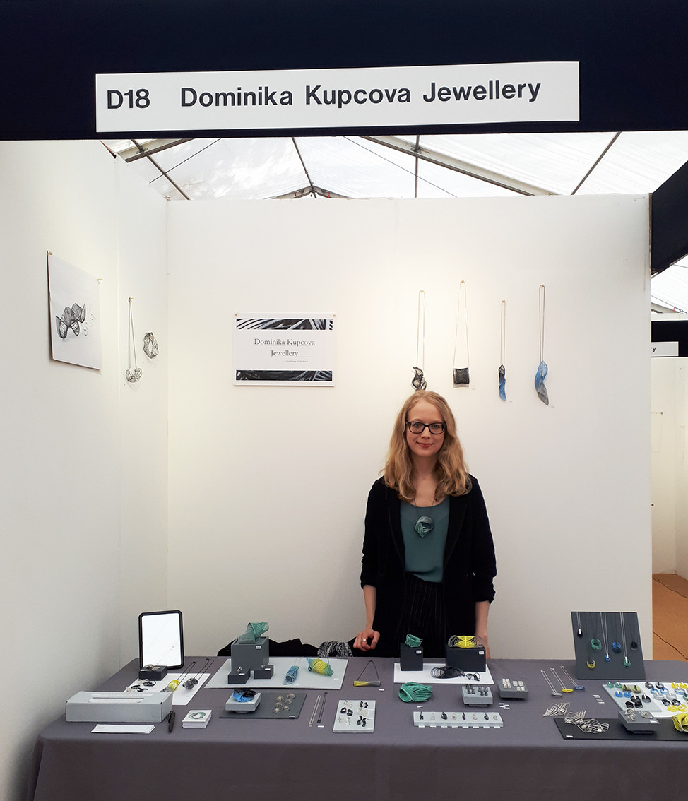Dominika standing at her Craft Festival stand, with her jewellery displayed on the table and on the walls behind her