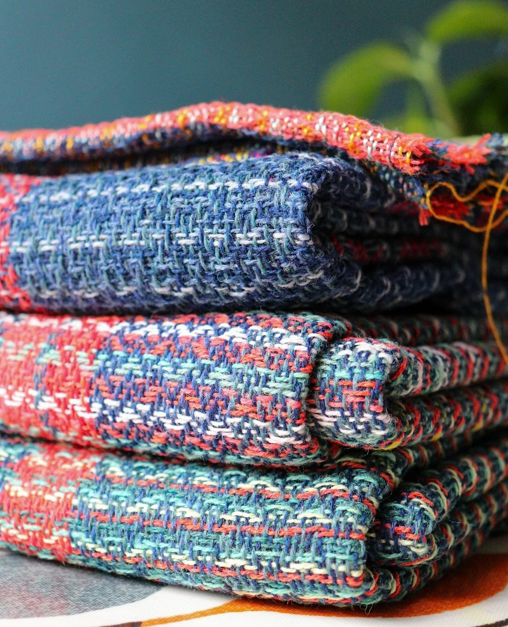 Close up of woven scarves that are folded and sitting on top of each other. They have beautiful weave patterns in red, blue, and mint green.