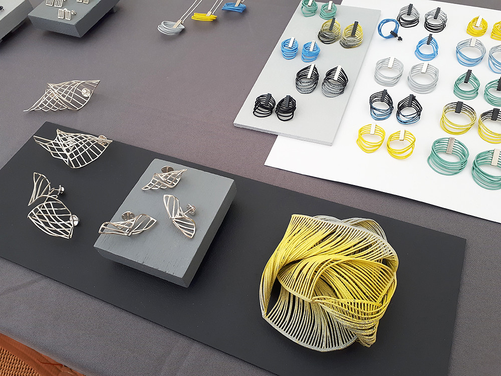 Photograph of a display of jewellery, a variety of silver and colourful card pieces including a statement yellow brooch, a selection of colourful earrings, and polished silver pins