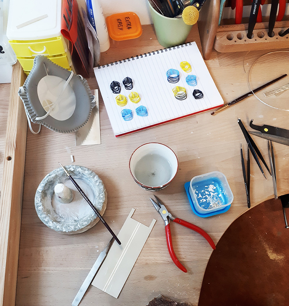 A close up of Dominika's jewellery bench, featuring a notebook that has colourful loop shapes sitting on it, a jewellery mask, a borax dish and cone, a sheet of polished silver, pliers, and other toold and tubs.