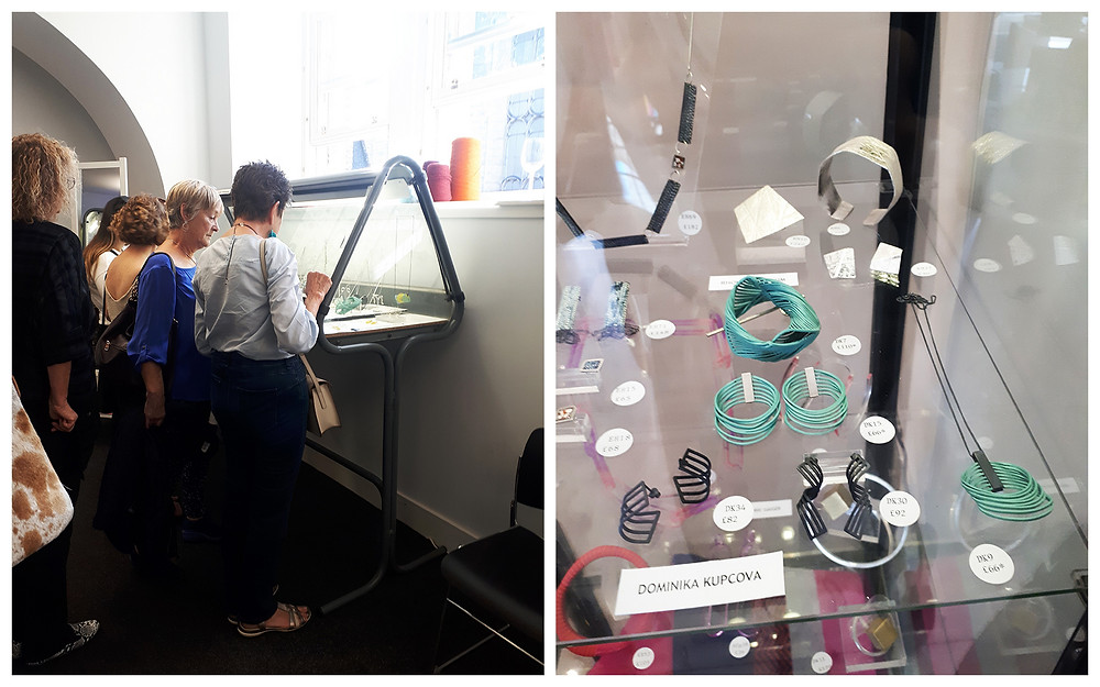 Photo 1 is of 2 white women looking at a glass display case in a Dazzle exhibition. They are both stylish women with short hair, one has blonde hair and is wearing a blue blouse, the other has dark spiky hair and is wearing a white shirt. Photo 2 is a close up of a Dazzle display of Dominika Kupcova Jewellery work, featuring earrings and other jewellery in mint green and black.