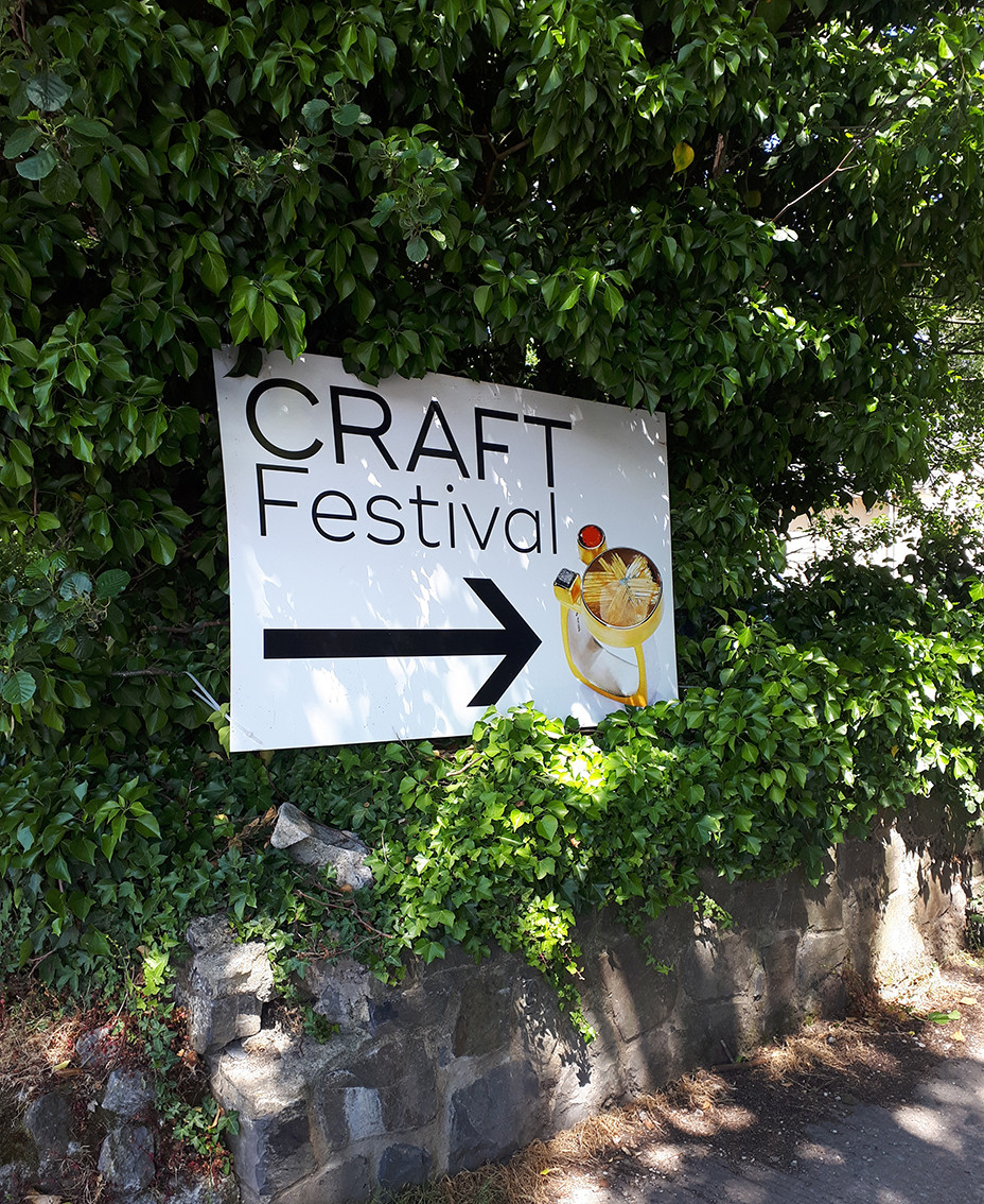 "Sign displayed on a hedge, saying ""Craft Festival"" and an arrow pointing to the right, with a photograph of a stone set ring"