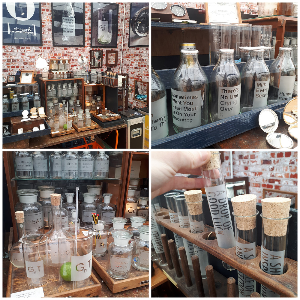 A collection of photos of the Vinegar & Brown Paper exhibition stand, showcasing a range of glass artworks with words etched on them, including milk bottles, apothercary jars, and test tubes.