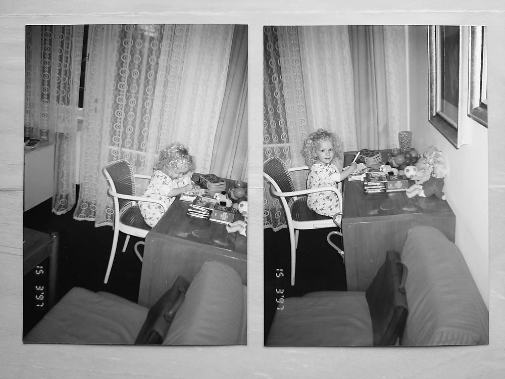 Two photos of Dominika at age 2 drawing at a wooden desk. She's sitting in a white chair and has lots of books and toys on the table. There are sheer white lace curtains behind her. In the left photo she is concentrating on the page, in the photo on the right she is looking straight at the camera and smiling gently. She has light blonde curly hair and is wearing a white patterned onesie.