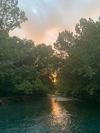 sunset betwen trees on lake.jpeg