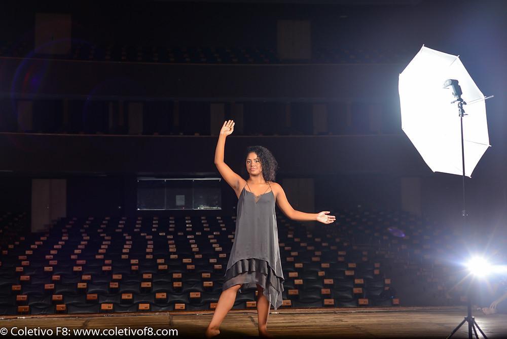 Bailarina no palco do teatro, com a plateia vazia ao fundo, e um flash com sombrinha ao lado.