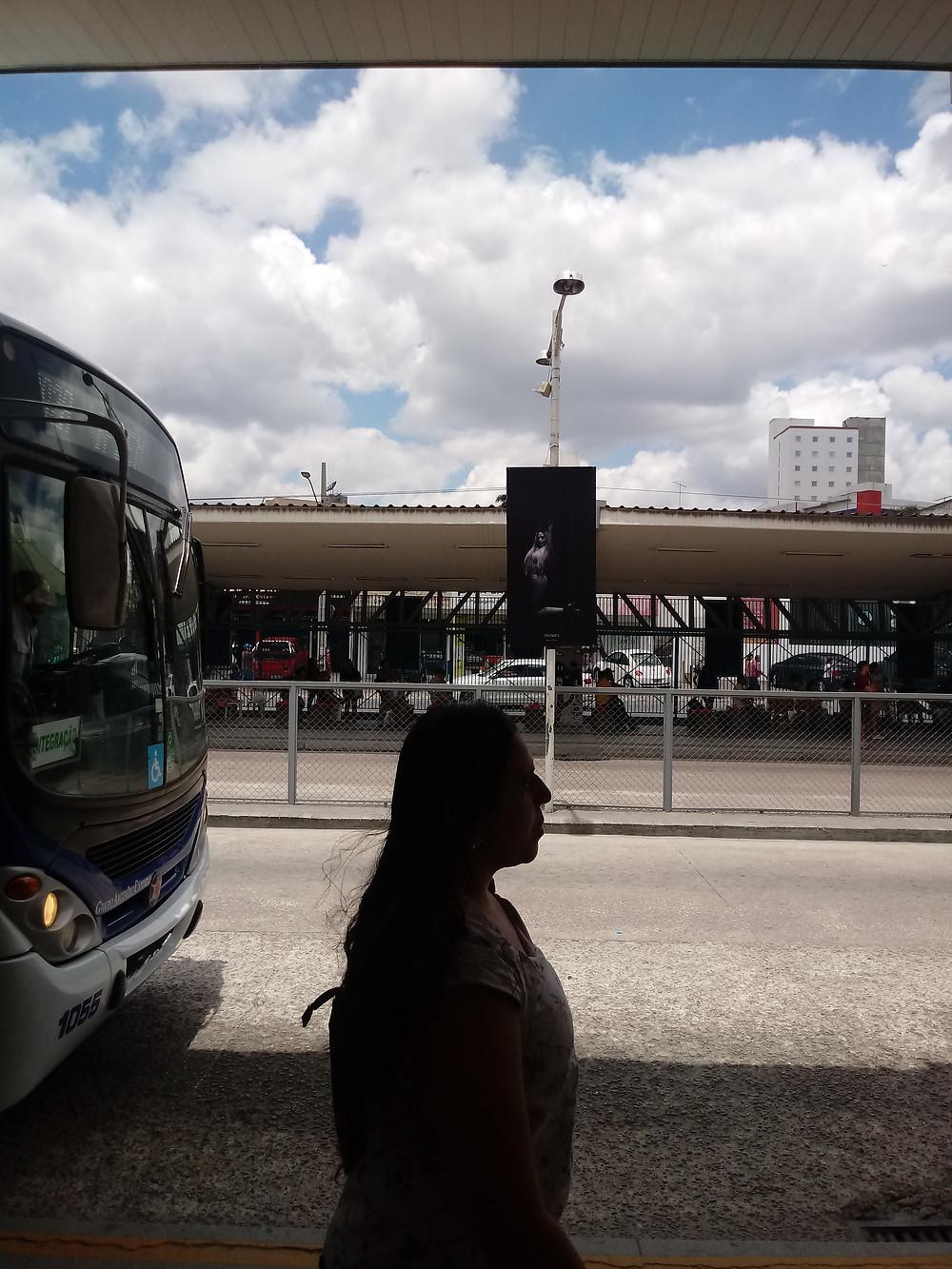 Passageira circula no Terminal de Ônibus com cartazes mostrando fotos sobre intolerância.