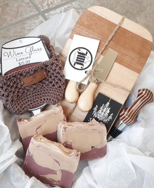 Gift basket with a winelanyard, cutting board, wine stopper, and hand made soap.